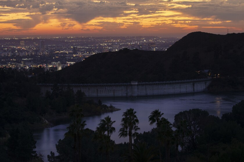 Passing rain clouds provide another colorful sunset as seen over the Hollywood Reservoir on Thursday.