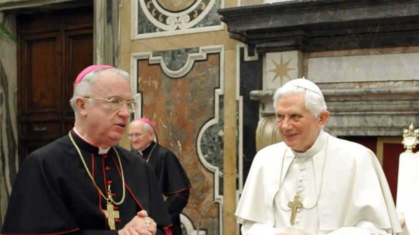 Pope Benedict XVI is presented with a birthday cake by Bishop Michael J. Bransfield, left, the presi
