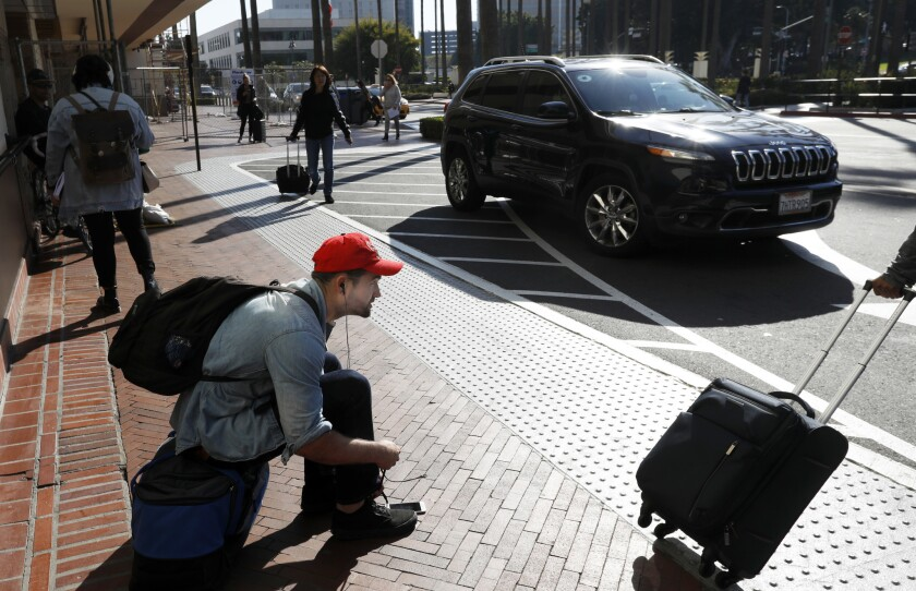 LOS ANGELES, CA February 25, 2019: William Miller, 24, of Los Angeles ties his shoes as he waits f