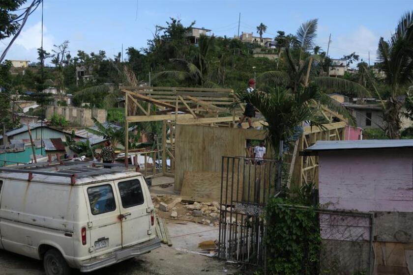 Fotografía que muestra a varios voluntarios que trabajan en el tejado de una residencia en el Barrio San Isidro, en el municipio de Canóvanas, al este de Puerto Rico. EFE/Archivo