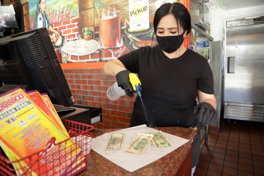 Maricela Moreno, a cashier at El Tarasco in Marina del Rey, sprays bills with alcohol at the restaurant. She said a lot of customers pay with Apple Pay or credit cards.