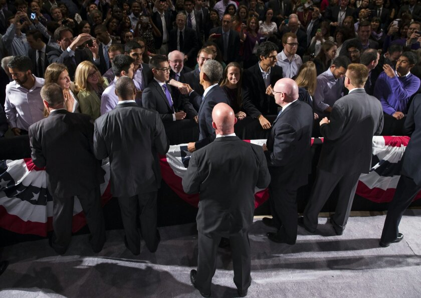 Secret Service agents surround President Barack Obama as he greets guests after speaking about the economy, Thursday, Oct. 2, 2014, at Northwestern University in Evanston, Ill. Obama is looking to frame the closing economic arguments of the midterm campaign. (AP Photo/Evan Vucci)