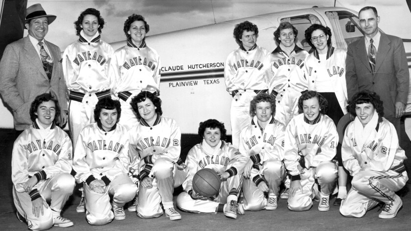Members of the Wayland Baptist basketball team pose for a photo in front of a private plane that transported them to games during an era in which the school dominated women's basketball.