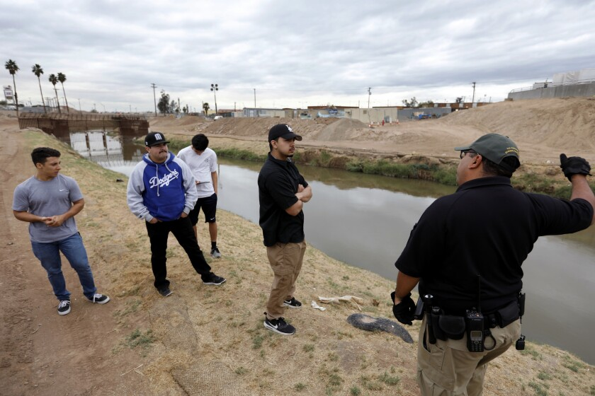 Joel Merino, right, of the Border Patrol instructs trainees on the hazards of the New River.