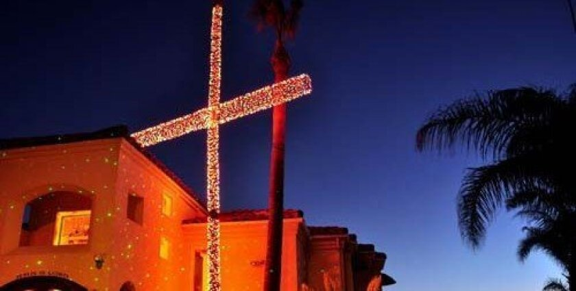 A lighted cross shines over the Kholi home in Bird Rock. Photo: Greg Wiest