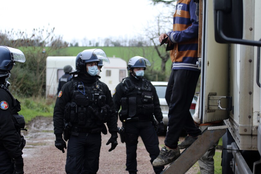 In this photo providedby the French Gendarmerie, a man exists a vehicle after being checked by gendarmes, near Lieuron, Brittany, France, Saturday, Jan. 2, 2021. A French prosecutor said police detained seven people Saturday, including two alleged organizers, after a New Year's Eve rave party drew at least 2,500 people in western France despite a coronavirus curfew and other restrictions. (Gendarmerie Nationale via AP)