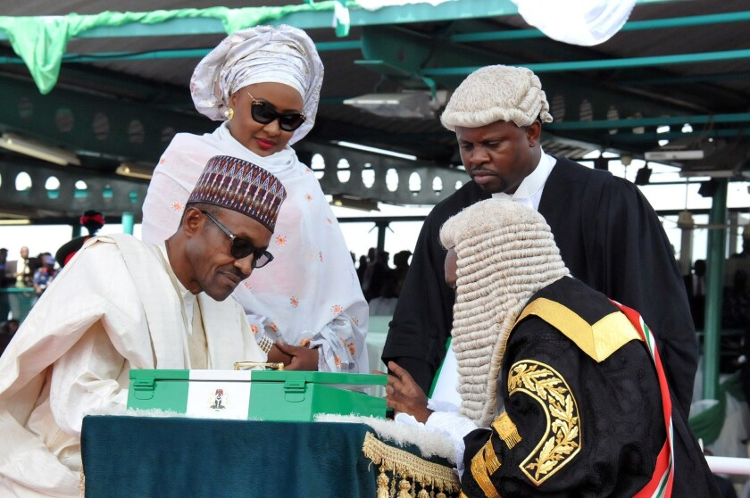 Nigerian President Mohammadu Buhari, left, sits beside his wife, Aisha, as he signs after swearing to an oath during his inauguration at Eagle Square in Abuja on Friday.