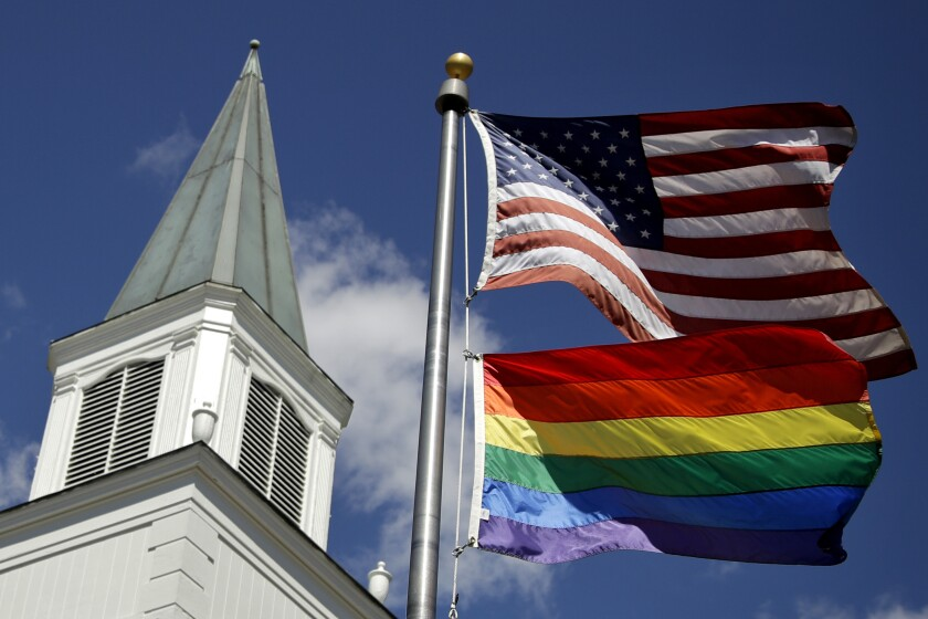 A gay pride rainbow flag flies along with the U.S. flag in front of the Asbury United Methodist Church in Kansas.
