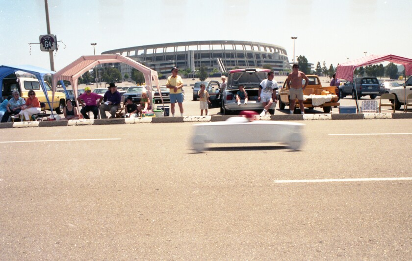 A soap box derby car crosses in a blur with stadium in background