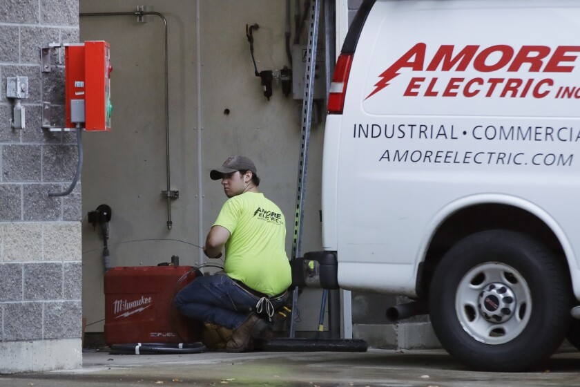 In this Wednesday, Oct. 2, 2019, photo, an electrician works at a car wash in North Andover, Mass. On Thursday, Oct. 3, the Institute for Supply Management, a trade group of purchasing managers, issues its index of non-manufacturing activity for September. (AP Photo/Elise Amendola)