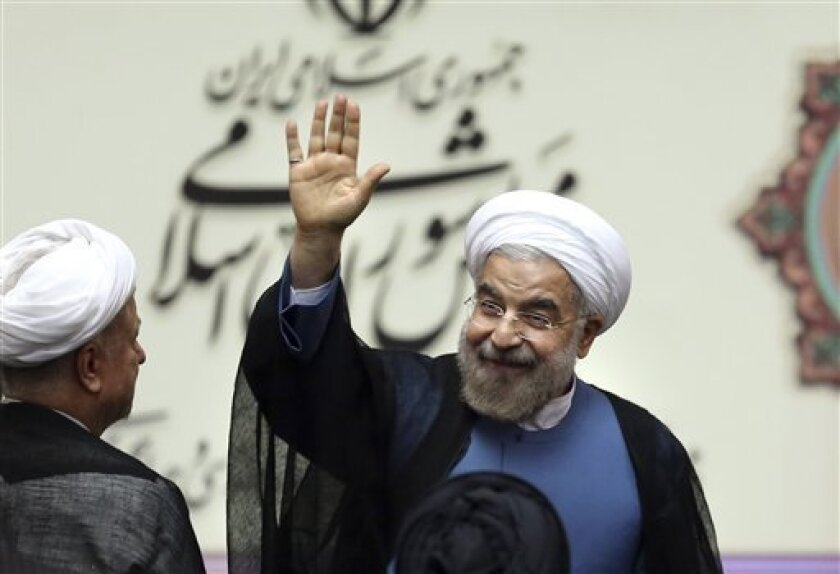 "Iran's new President Hasan Rouhani, waves after swearing in at the parliament, in Tehran, Iran, Sunday, Aug. 4, 2013. Iran's new president on Sunday called on the West to abandon the ""language of sanctions"" in dealing with his country over its contentious nuclear program, hoping to ease the economic pressures now grinding its people. Rouhani spoke after being sworn in as president in an open session of parliament Sunday, capping a weekend that saw him endorsed by Ayatollah Ali Khamenei, Iran's s"