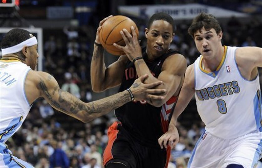 Toronto Raptors guard DeMar DeRozan (10) drives past Denver Nuggets forward Kenyon Martin, left, and Danilo Gallinari (8), from Italy, during the first quarter of an NBA basketball game in Denver, Monday, March 21, 2011. (AP Photo/Jack Dempsey)