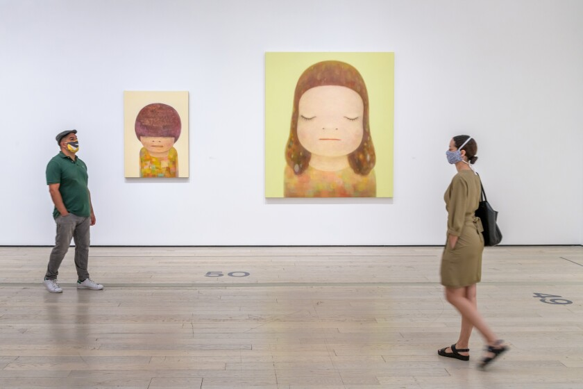 Masked gallery-goers walk past paintings by Yoshitomo Nara at the newly reopened Los Angeles County Museum of Art.