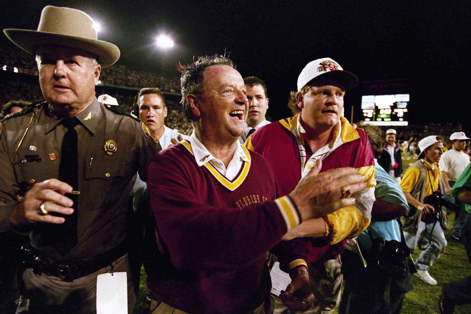 Bobby Bowden, smiling, stands with a crowd of other people on the football field.