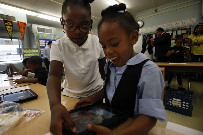 Students at Broadacres Avenue Elementary School in Carson examine new iPads purchased by the L.A. Unified School District in 2013.