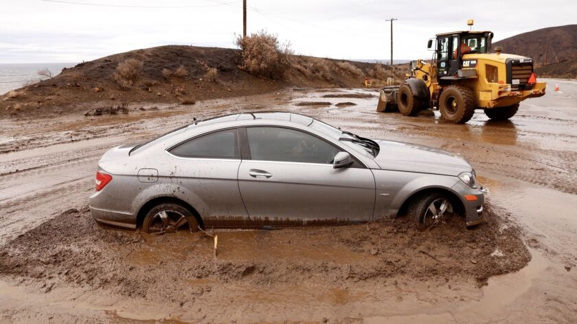A car was caught in a mudflow on Pacific Coast Highway in Malibu Thursday morning after rain showers doused the Southland.