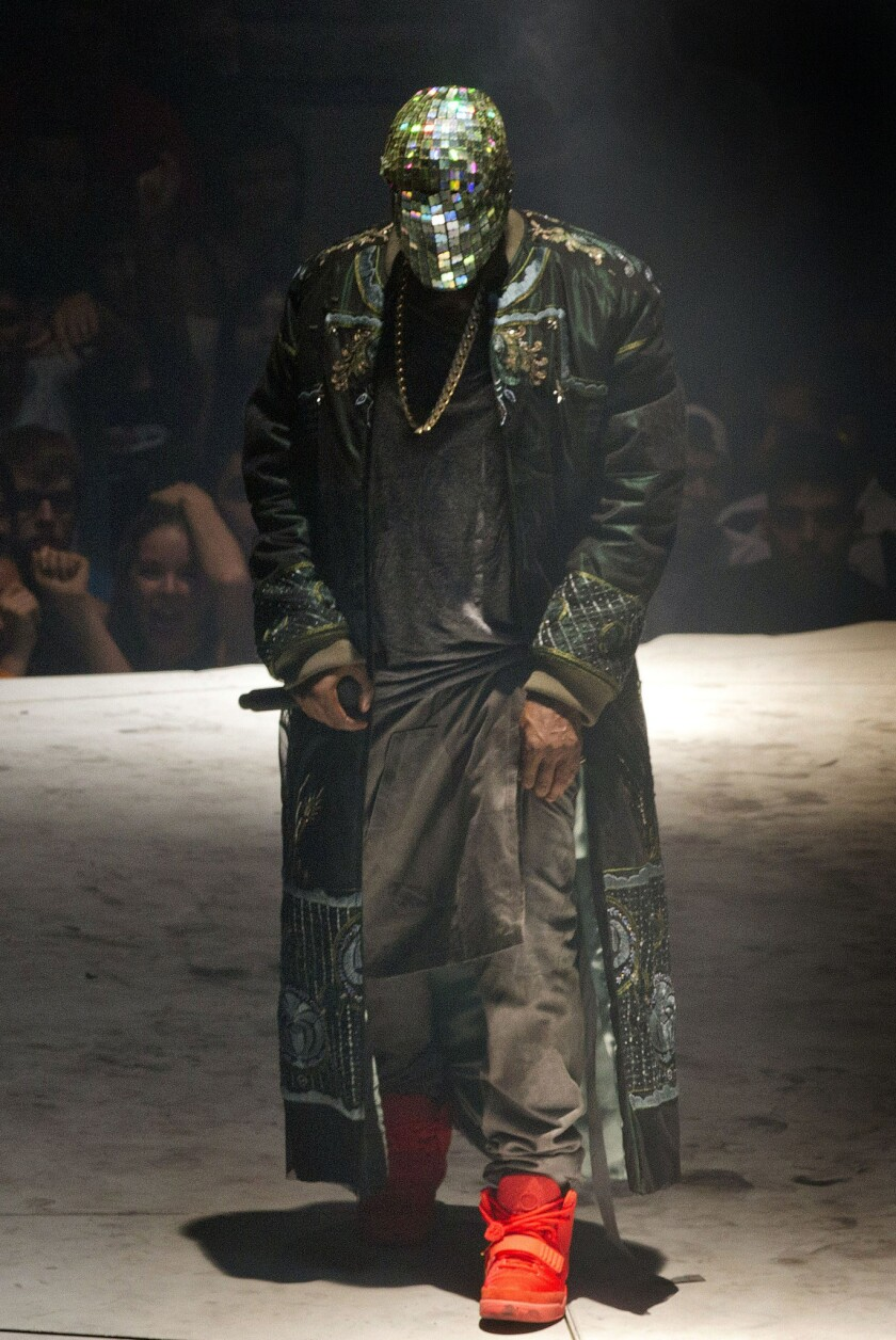"""Kanye West wears custom-made Maison Martin Margiela to kick off his """"Yeezus"""" tour in Seattle on Saturday night. The label announced has created a range of custom pieces for the tour, including bomber jackets, silk trousers and face-obscuring veils."""