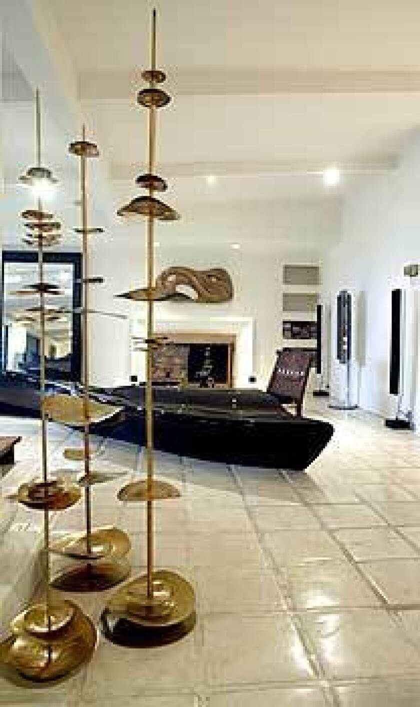 Adam Isaacs admits he fell for this Century City condo because it fit his couch. But this is not any couch: It's a sculpture-sofa by recent Pritzker winner Zaha Hadid. White Mexican pavers create a stage for the Hadid sofa and cymbal-like brass sculptures by jeweler Robert Lee Morris.