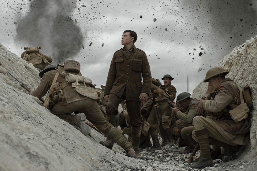 "George MacKay stands in a foxhole among others in WWI costumes in the movie ""1917."""