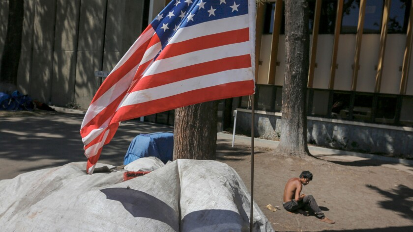 An American flag flies over a homeless encampment in the Civic Center Plaza in Santa Ana.