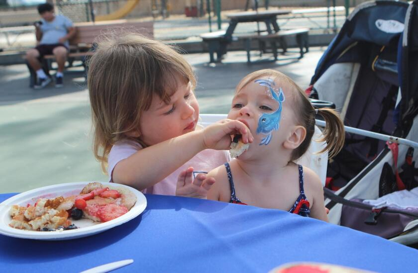 Naomi Barry, 3, feeds her cousin Coral Barry, 2, some pancakes and some love.