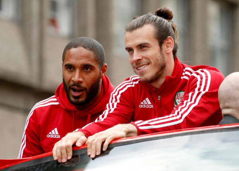 Wales soccer players ride an open top bus, with front left to right, Ashley Williams, Gareth Bale, as they acknowledge the crowd of fans during their homecoming in Cardiff City centre, Wales, Friday July 8, 2016.  Wales return home to a hero's welcome after unexpectedly reaching the semi-finals of
