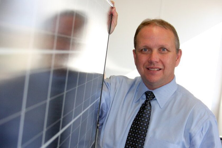 Steve Hill, who heads Kyocera's North American solar subsidiary, held one of the company's solar modules. Kyocera has announced that it will begin manufacturing panels in San Diego.