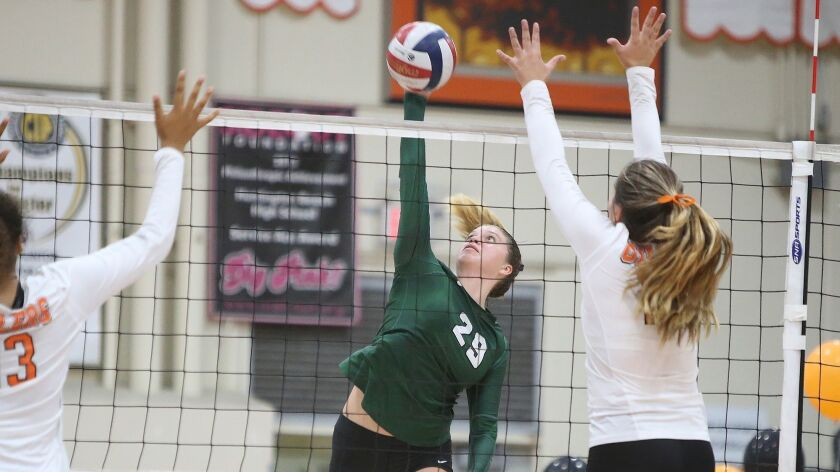 Edison's Nikki Logan puts the ball past two Huntington blockers in girls volleyball on Tuesday at Hu