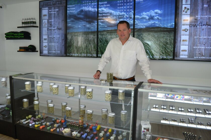Chris Murray, co-owner of ShowGrow, stands in a secured room behind a case of medical cannabis products with a menu board behind him displaying prices.