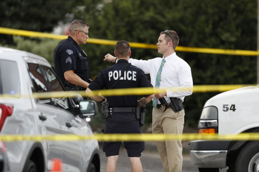 Law enforcement officials investigate the scene of a shooting in a parking lot behind a dental clinic, on June 14, 2018, in Westminster, Colo.
