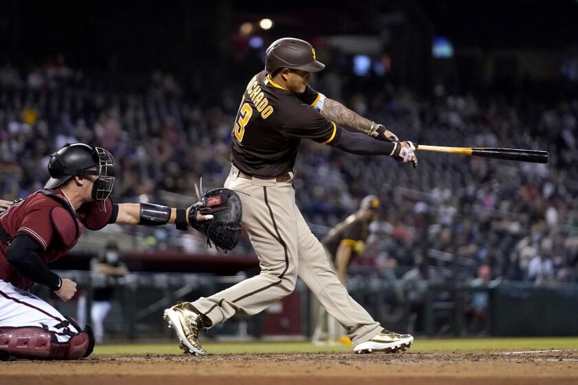 Manny Machado, de los Padres de San Diego, sacude un triple de tres carreras ante el catcher de los Diamondback