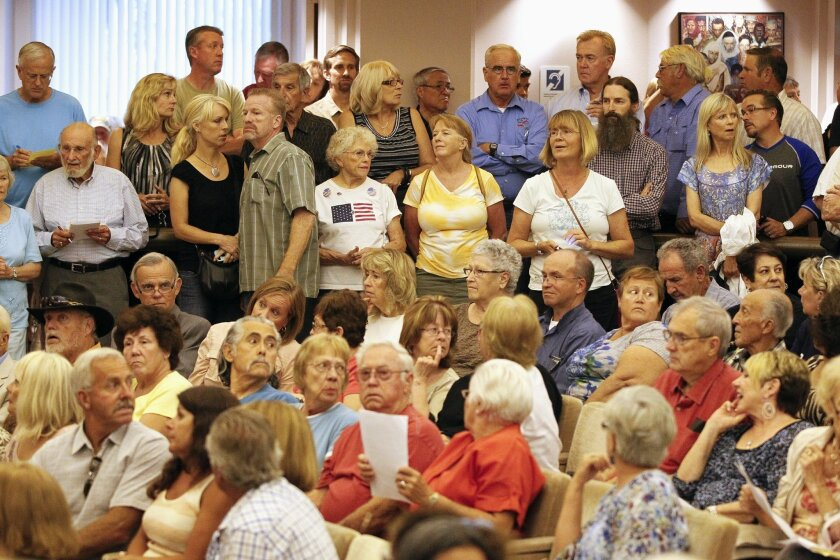 """People packed into the Escondido City council Chambers listen as the Escondido Planning Commission holds a meeting June 24, 2014 considering a request for a conditional use permit to convert a 96-bed skilled nursing facility to an """"Unaccompanied Youth Care Center."""""""