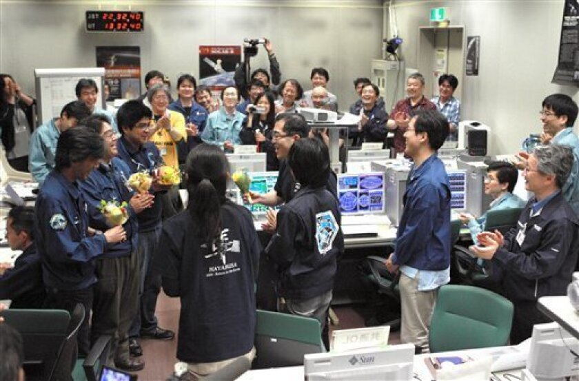 Project Manager Junichiro Kawaguchi, right in foreground, as other engineers engaged in Hayabusa probe asteroid exploration project celebrate with flowers after the probe's detached sampler capsule was confirmed to reenter Earth's atomosphere, in the control center at Japan Aerospace Exploration Ag