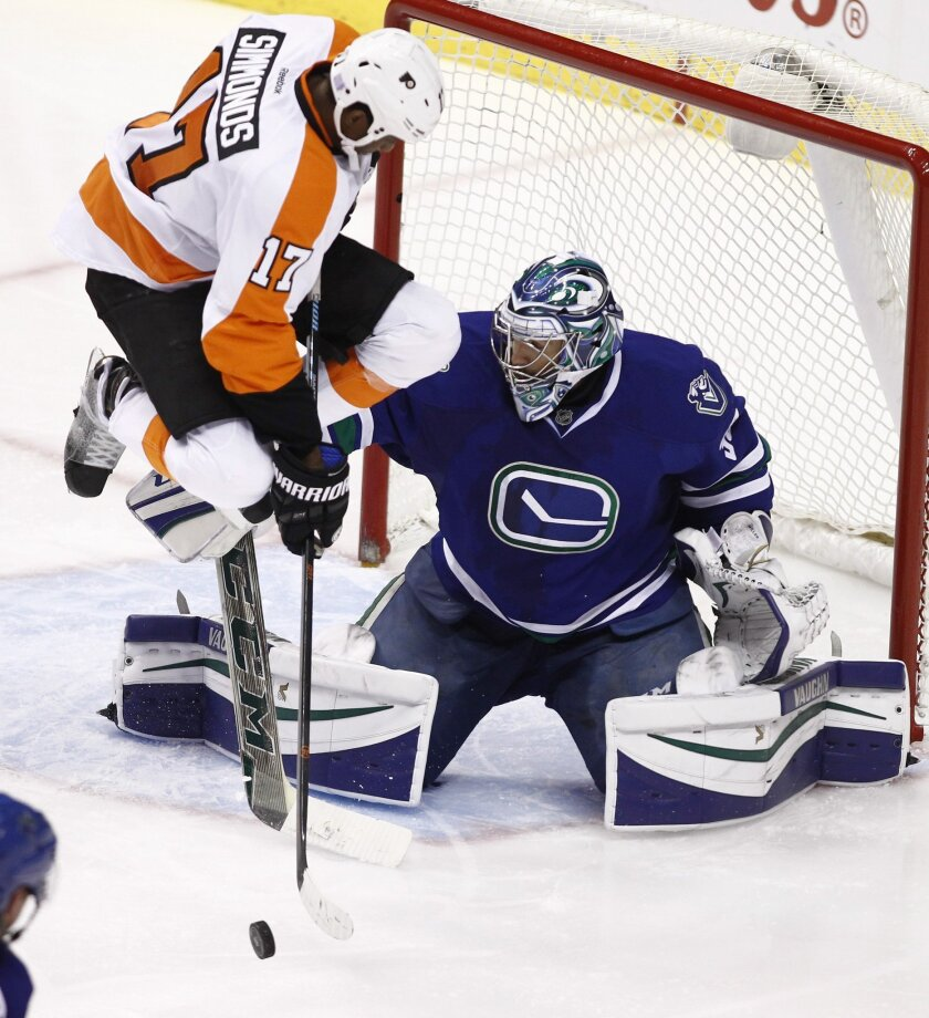 Philadelphia Flyers' Wayne Simmonds (17) tips the puck in front of Vancouver Canucks goaltender Ryan Miller (30) during third period NHL hockey action in Vancouver, British Columbia, on Monday, Nov. 2, 2015. (Ben Nelms/The Canadian Press via AP)