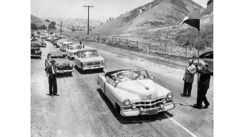 Cars line up on Malibu Canyon Road as a man holds a flag on a tall pole