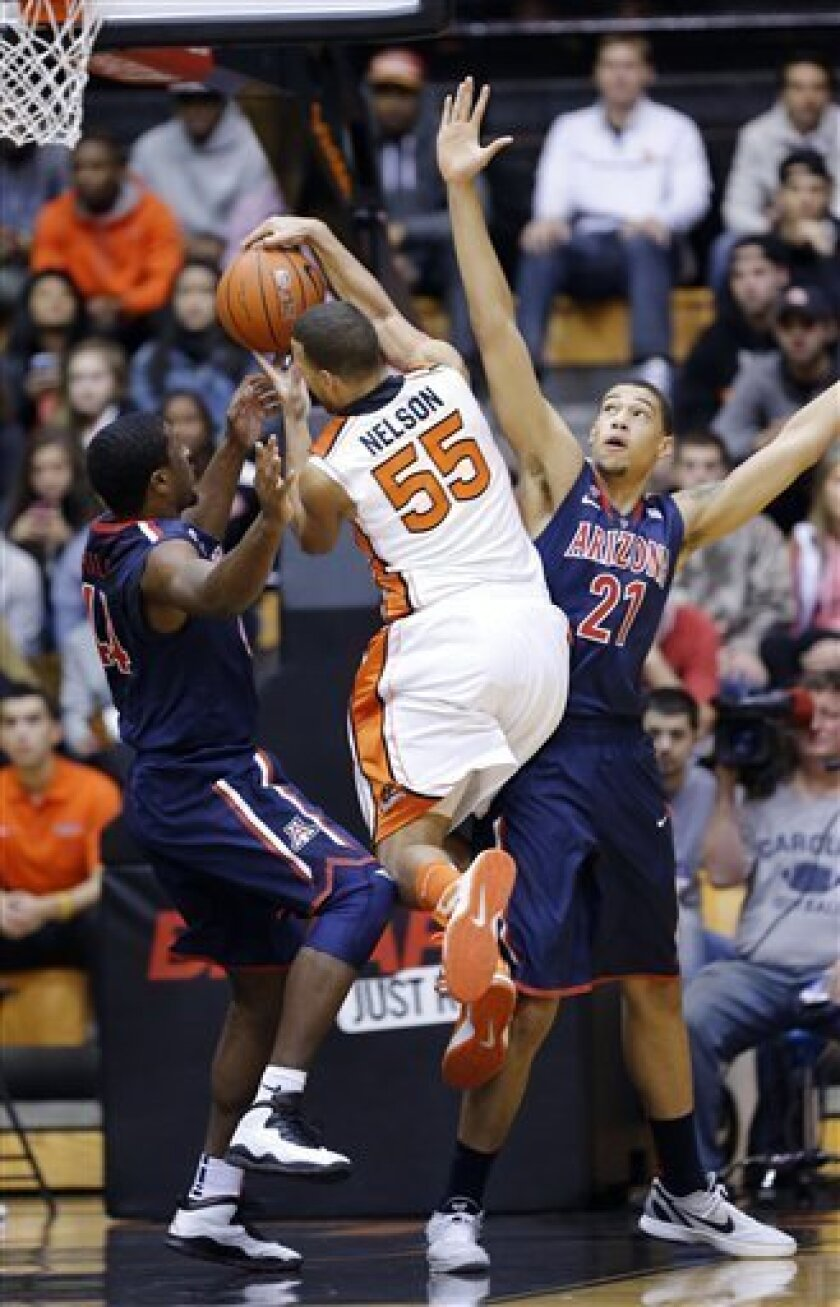 Oregon State forward Drew Mellon, middle, drives between Arizona's Solomon Hill,left, and Brandon Ashley on his way to the basket during the first half of an NCAA college basketball game in Corvallis, Ore., Saturday, Jan. 12, 2013. (AP Photo/Don Ryan)