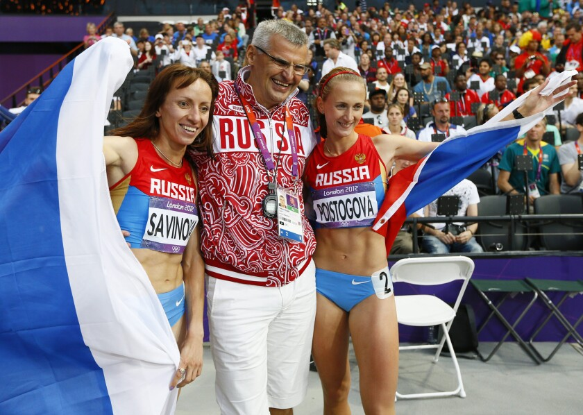 Russian athletes Mariya Savinova and Ekaterina Poistogova celebrate with Coach Vladimir Kazarin after the women's 800m final at the 2012 Olympic Games. Both athletes are among five Russian runners targeted for a lifetime ban.