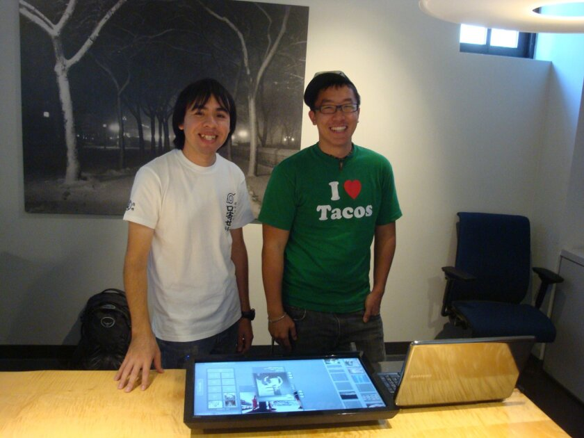 Lance Castillo and Wesley Hsu pose with their touch table, which allows museum visitors to interact with photos in an exhibit. Courtesy