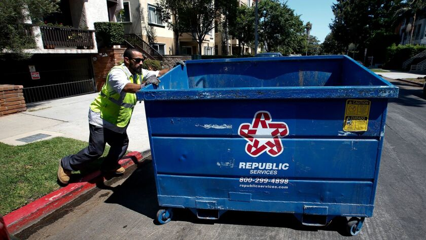An employee with the trash hauler Athens Services moves a refuse bin outside a 14-unit condominium b