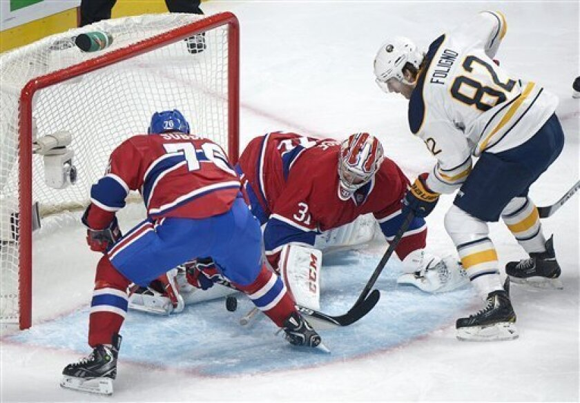 Montreal Canadiens' goaltender Carey Price makes a save against Buffalo Sabres' Marcus Foligno (82) as Canadiens' P.K. Subban moves in during the second period of  an NHL hockey game in Montreal, Saturday ,Feb. 2, 2013. (AP Photo/The Canadian Press, Graham Hughes)