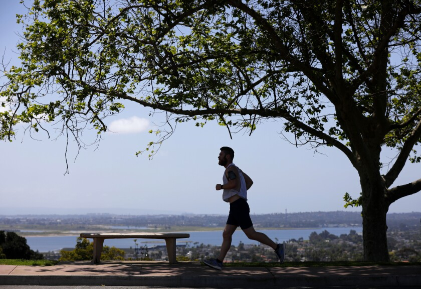 A runner jogs along the sidewalk at Kate Sessions Neighborhood Park in Pacific Beach on Tuesday, April 21, as San Diego neighborhood parks reopened for limited use.