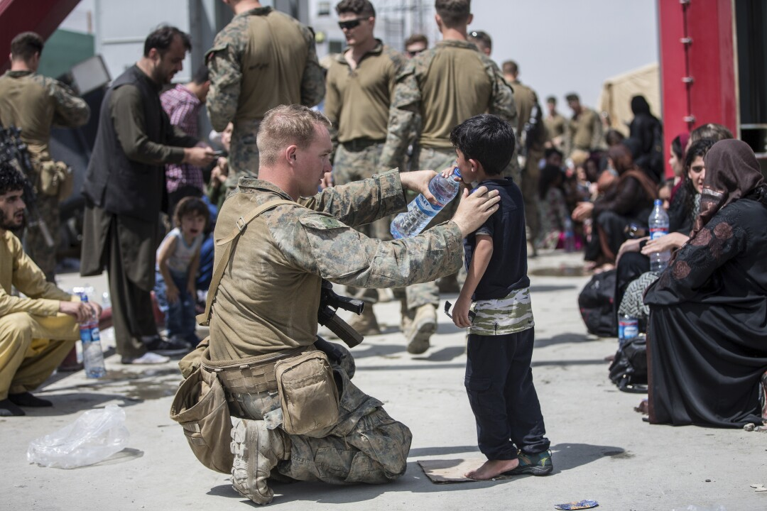 A U.S. Marine with the 24th Marine Expeditionary Unit (MEU) provides fresh water to a child during an evacuation