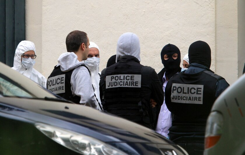 French police officers stand outside a villa during a search operation for what could be a major stash or arms in Biarritz, southwestern France, Thursday, May 28, 2015. French and Spanish authorities have detained one person and are raiding a villa in the French Atlantic coast city of Biarritz, in an operation targeting the Basque separatist group ETA. (AP Photo/Bob Edme)