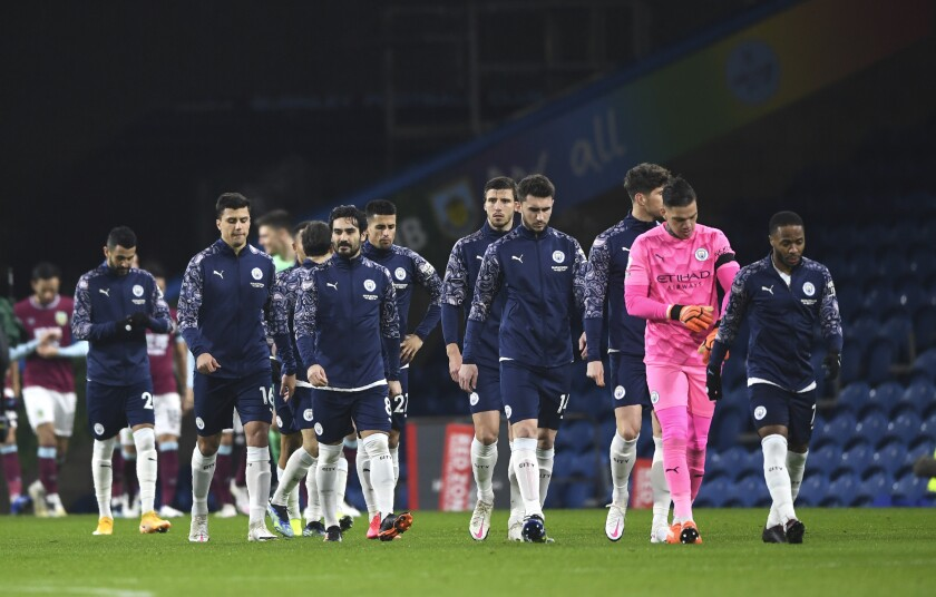 Manchester City players arrive on the pitch in front of many empty seats prior the English Premier League soccer match between Burnley and Manchester City at Turf Moor stadium in Burnley, England, Wednesday, Feb. 3, 2021. (Gareth Copley/Pool via AP)