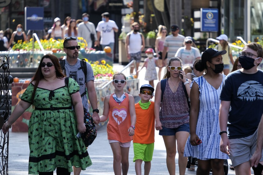 FILE - In this June 15, 2021, file photo, people arrive at Universal Studios in Universal City, Calif. Many Americans are relaxing precautions taken during the COVID-19 pandemic and resuming everyday activities, even as some worry that coronavirus-related restrictions were hastily lifted, according to a new poll from The Associated Press-NORC Center for Public Affairs Research. (AP Photo/Ringo H.W. Chiu, File)