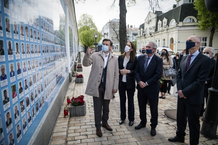 Left to right, Ukrainian Foreign Minister Dmytro Kuleba, Belgium's Foreign Minister Sophie Wilmes, Luxembourg's Foreign Minister Jean Asselborn and Foreign Minister of Netherlands Stephanus Blok lay flowers at the Memorial Wall of Fallen Defenders of Ukraine in Russian-Ukrainian War in Kyiv, Ukraine, Friday, May 7, 2021. (Ukrainian Foreign Minister Press Office via AP)
