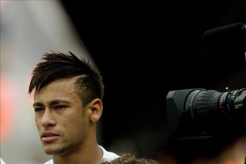 El delantero brasileño Neymar, que firmará un contrato para las próximas cinco temporadas con el equipo español del Barcelona, llora durante el himno nacional brasileño previo a jugar su último partido en el Santos enfrentando al Flamengo. EFE