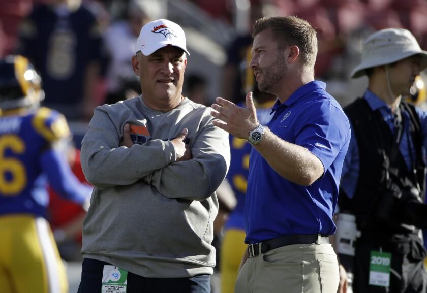 Denver Broncos coach Vic Fangio, left, speaks with Los Angeles Rams coach Sean McVay.