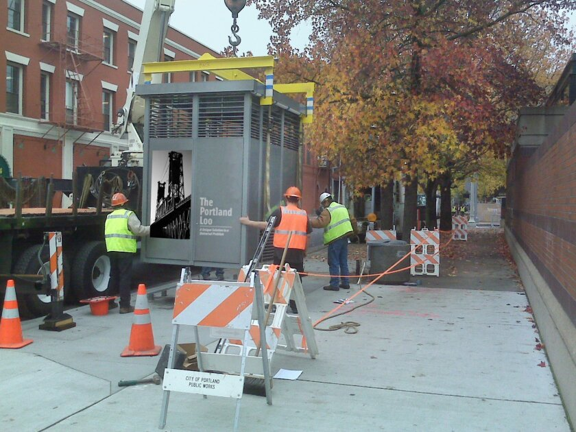 Construction crews install a Portland Loo public restroom, made of stainless steel  and painted with an anti-graffiti coat.