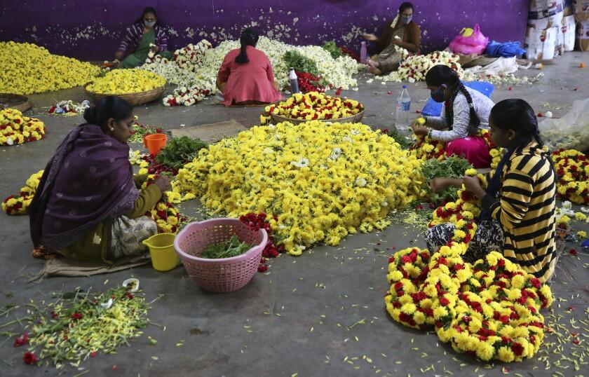 Vendedoras de flores, algunas con mascarilla para protegerse del coronavirus, preparan guirnaldas en un mercado en Bengaluru, India, el 24 de septiembre de 2020. (AP Foto/Aijaz Rahi)